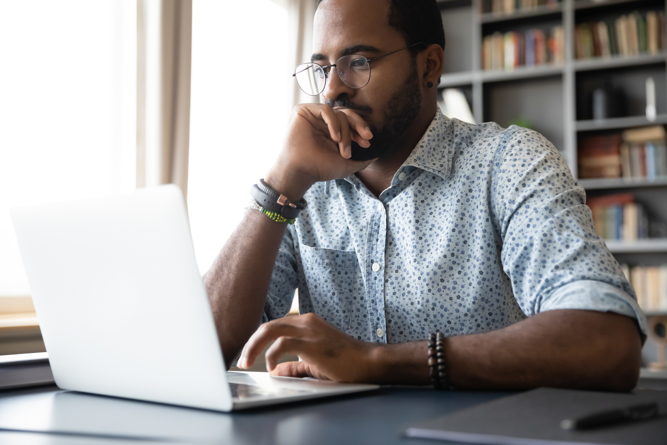 Male African American Business owner looking at his laptop with focus